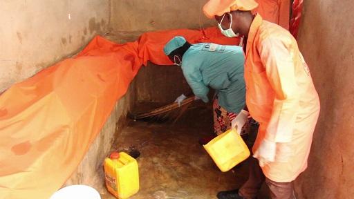 Des embaumeurs évacuant les déchets liquides issus des cadavres dans une fosse sceptique.